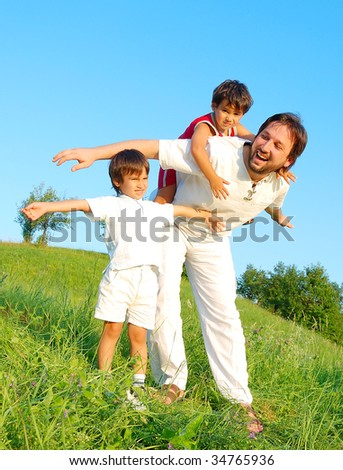 Young father in white with boys on beautiful meadow - stock photo