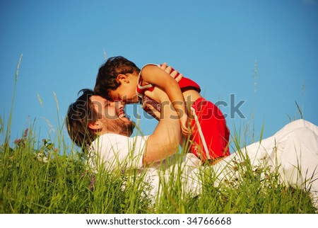 Young father in white with child on beautiful meadow - stock photo