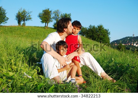 Young father in white with children on beautiful meadow - stock photo