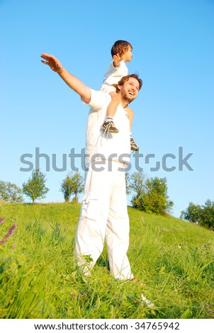 Young father in white with little boy on beautiful meadow - stock photo