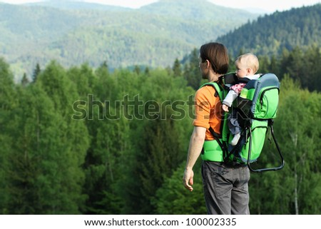 Young father is hiking with one year old son in baby carrier - stock photo