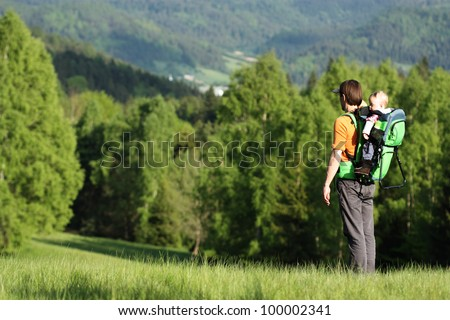 Young father is hiking with one year old son in baby carrier