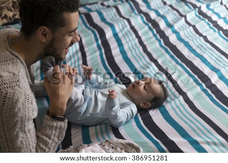 Young father is playing lovingly with his baby son, who is lying on his parents bed.