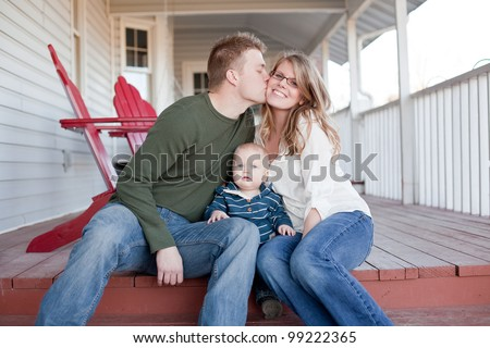 Young father kisses his wife with son on the porch. - stock photo
