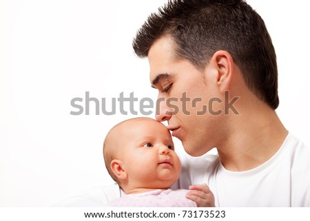 Young father kissing his angelic two months daughter - stock photo