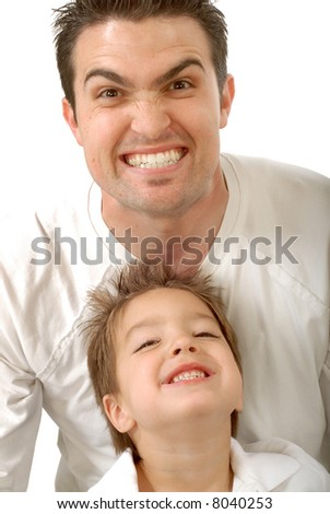 Young father making funny scary faces with his little son - stock photo
