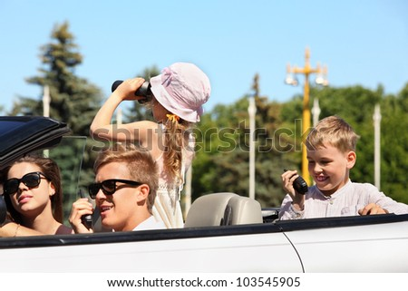 Young father, mother and two children ride in convertible car and play at summer day - stock photo