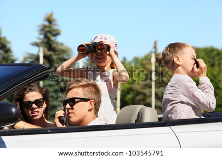 Young father, mother and two children ride in convertible car and play spies - stock photo