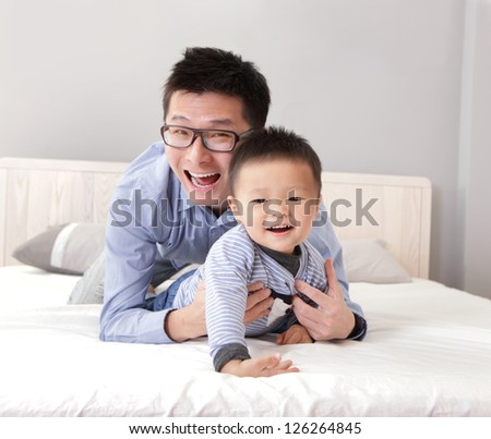 young father play with his son boy on the bed at home, asian lifestyle - stock photo