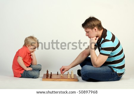 Young father playing chess with his little cute son - stock photo