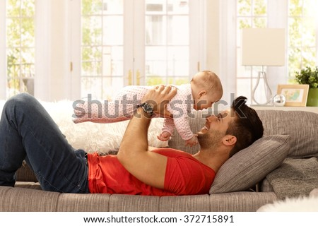 Young father playing with baby daughter on sofa. Side view. - stock photo