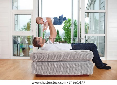 Young father playing with baby while lying on couch