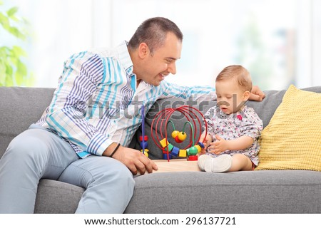 Young father playing with his baby daughter seated on a gray sofa at home  - stock photo