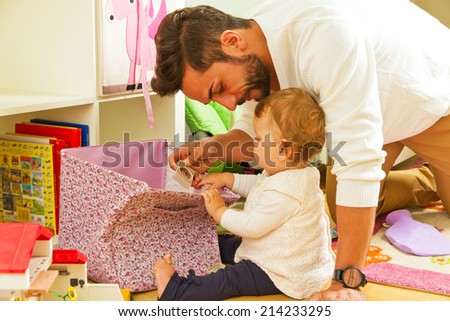 Young father playing with his baby girl - stock photo