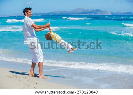 Young father playing with his son on tropical beach vacation