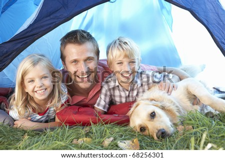 Young father poses with children in tent - stock photo