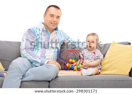 Young father posing seated on a gray sofa with his baby daughter isolated on white background - stock photo