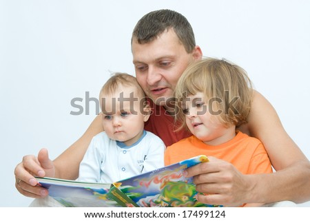 young father reading fairy tale to children - stock photo