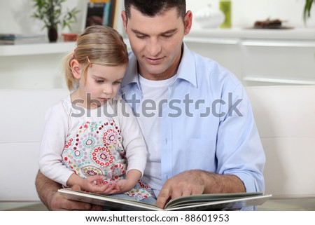 young father reading his daughter story - stock photo