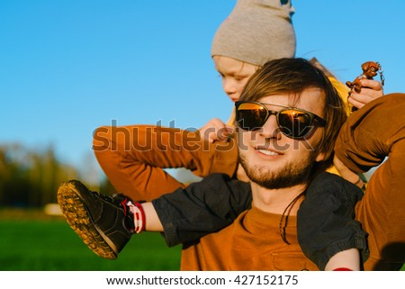 Young father resting with his young son on summer field at sunset - stock photo