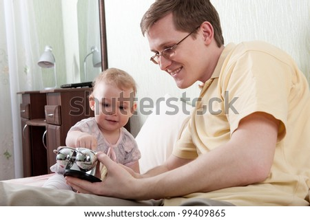 Young father showing alarm clock to his little daughter - stock photo