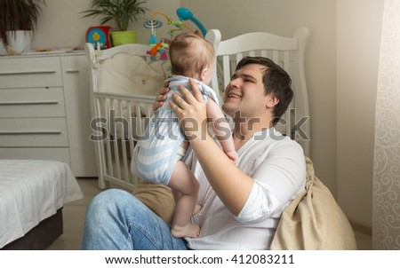 Young father sitting in bag chair and holding his little baby son - stock photo