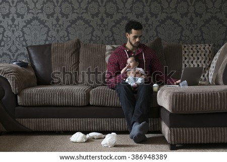 Young father sitting on his sofa at home with his baby son on his knee. He is working on a laptop and there are dirty nappies on the floor.