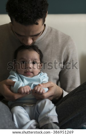 Young father sitting with his baby son in his lap. He is holding his hands and kissing him on his head. The baby is looking at the camera.