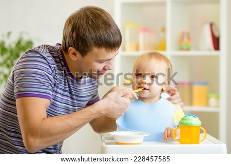 young father teaches his baby to eat with spoon - stock photo
