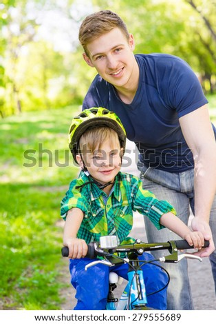 young father teaches his son to ride a bike - stock photo