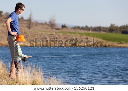 young father teaching his cute son fishing - stock photo