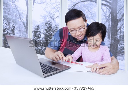 Young father teaching his female child on the table at home while using a book and laptop