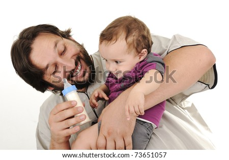 Young father trying to feed his little baby son in arms - stock photo