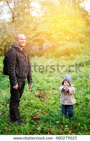 Young father walking and having fun with his cute little son