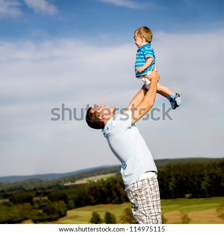 young father with a little son on the meadow - stock photo