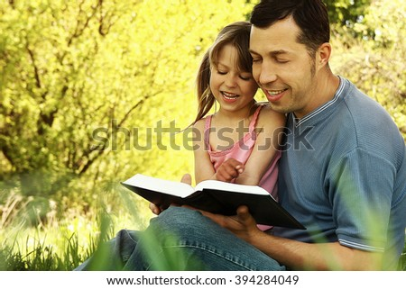 young father with a small daughter reading the Bible - stock photo