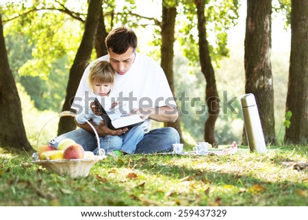 young father with a young daughter read the Bible in nature - stock photo