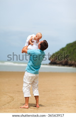 Young father with baby daughter at the beach