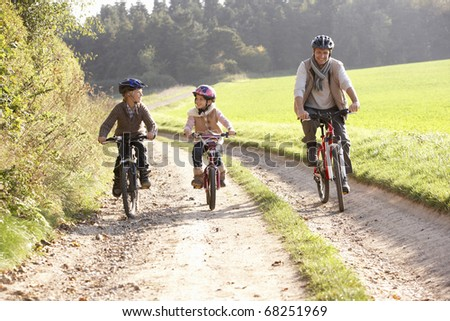 Young father with children ride bikes in park - stock photo