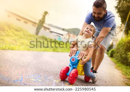 Young father with her little daughter on motorbike in green sunny park - stock photo