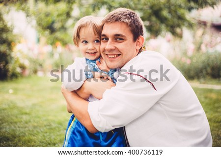 """Young father with his child in the garden. They is dressed in ethnic costumes. Ukrainian national costume is primarily """"vyshyvanka"""" (embroidered shirt).  - stock photo"""