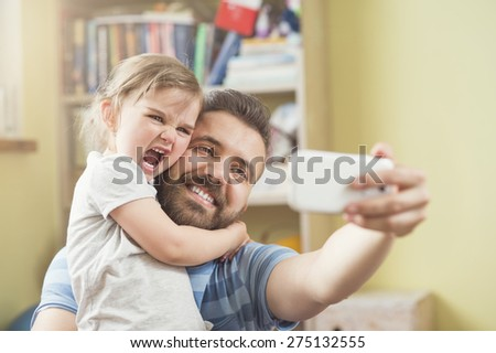 Young father with his cute little daughter taking selfie - stock photo
