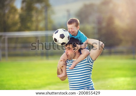 Young father with his little son having fun on football pitch - stock photo