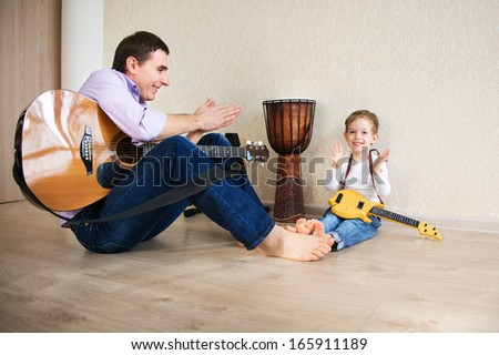Young father with his little son playing guitar - stock photo