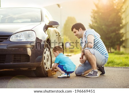 Young father with his little son washing car - stock photo