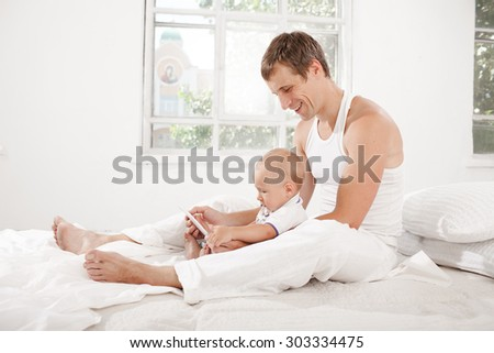 Young father with his nine months old son sitting on the bed at home on white home background with digital tablet