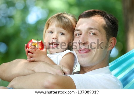 young father with his small daughter in a hammock