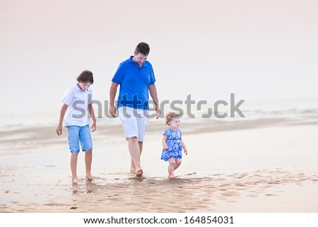 Young father with his son and toddler girl walking at the beach at sunset - stock photo