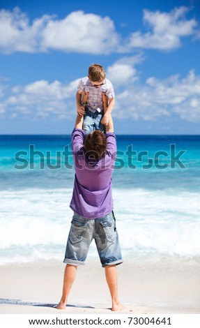 Young father with his son on beach vacation having fun - stock photo