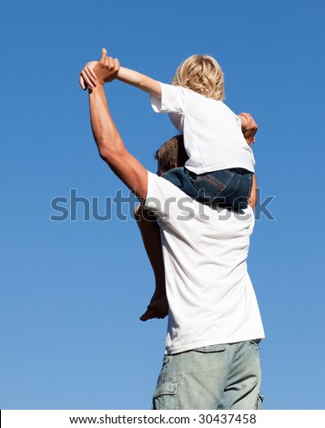 Young father with his son on his back - stock photo